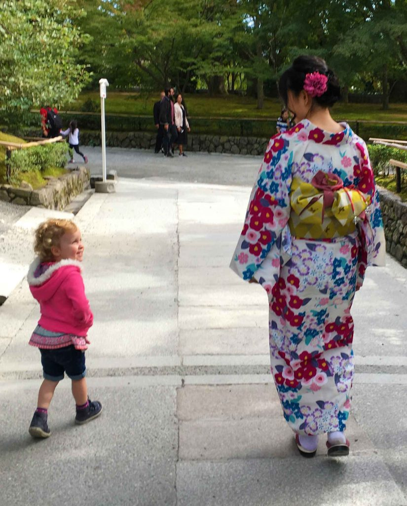A little girl smiles at a Japanese lady in a beautiful kimono at the Kyoto Golden Pavillion (Kinkakuji)
