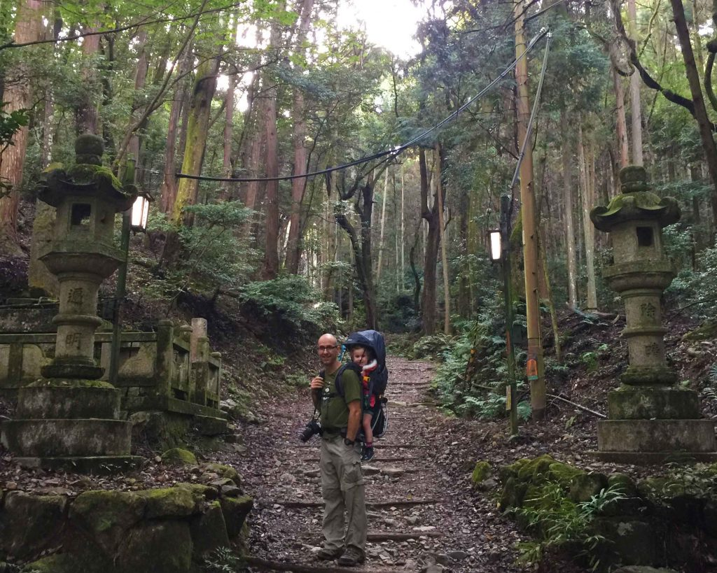 A father carries his toddler in a backpack carrier while hiking in Kyoto on the Daigoji trail