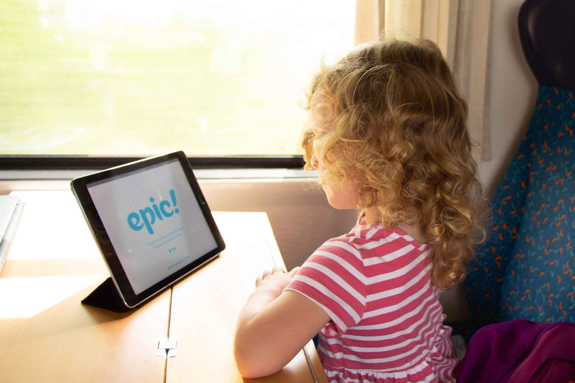 A child enjoying the Epic Reading App on a train