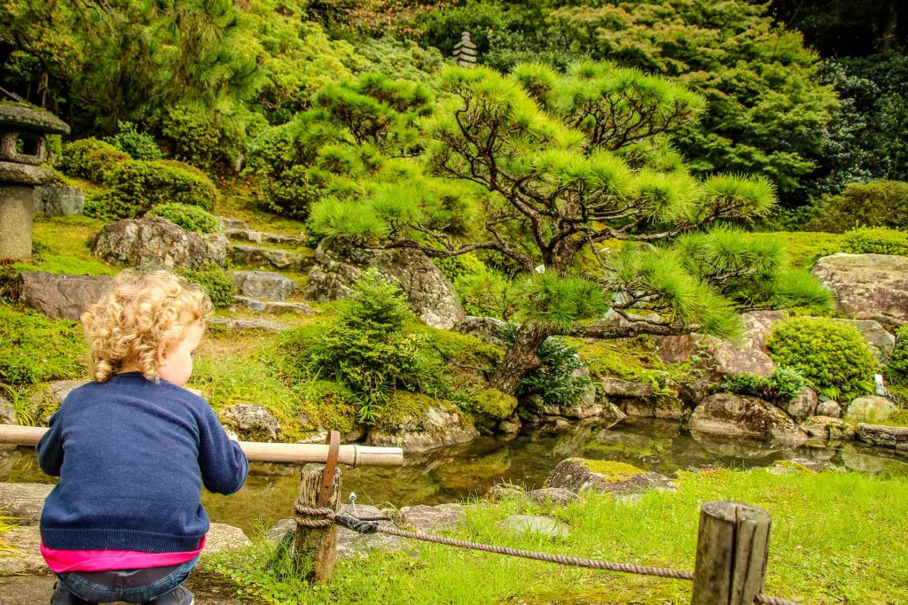 A toddler admires the beauty of the sculpted gardens in Ginkakuji Temple in Kyoto, Japan