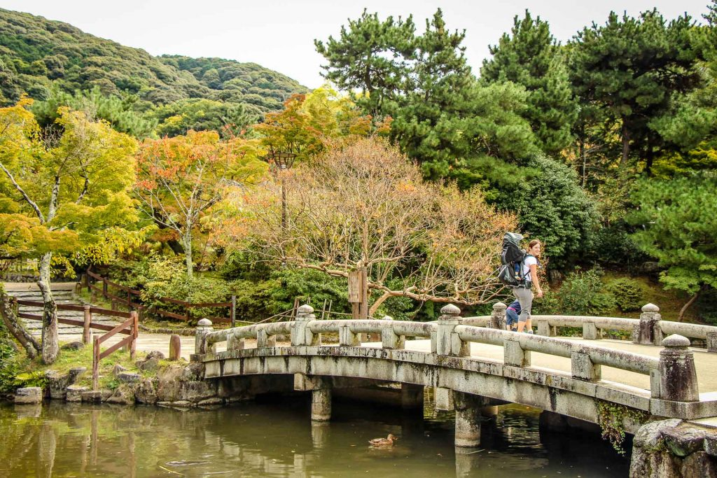 A family on vacation in Kyoto, Japan stops to enjoy the beauty of Maruyama Park