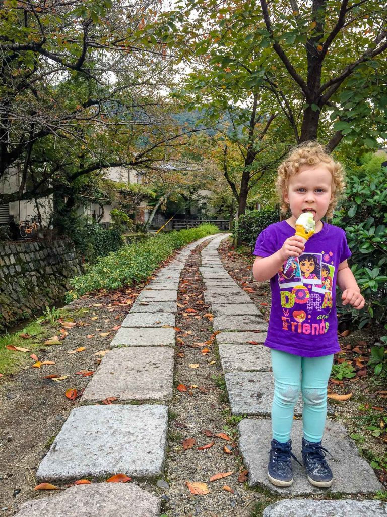 A girl enjoys matcha ice cream while walking the Philosophers Path in Kyoto Japan