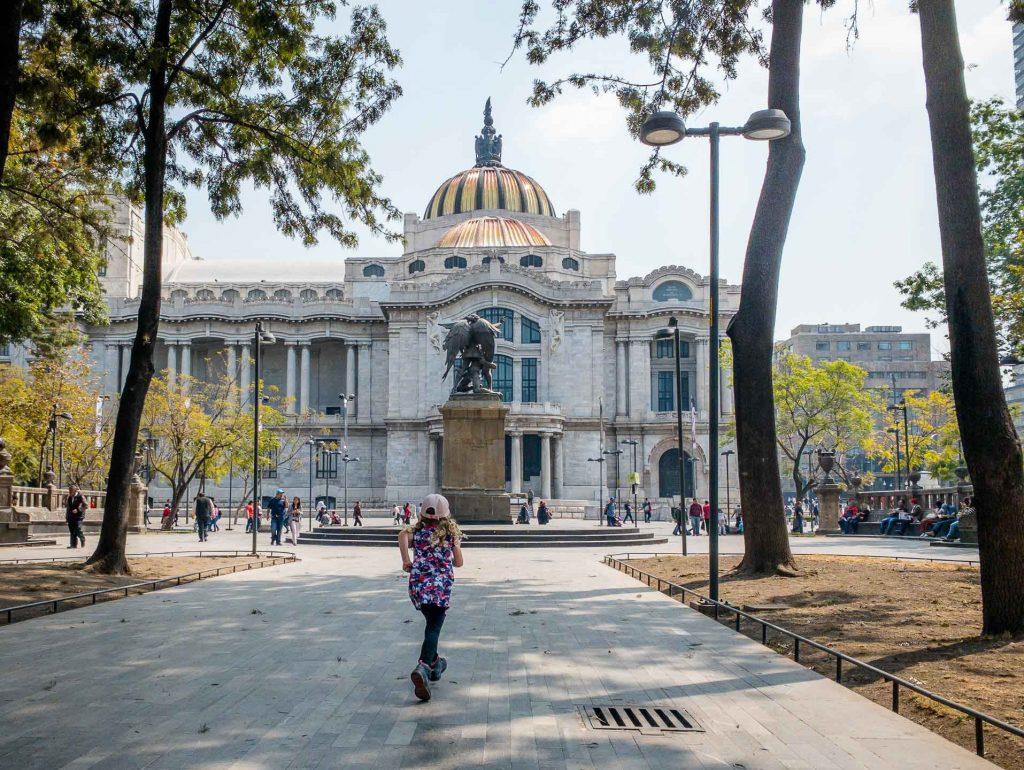 A girl runs towards Palacio de Bellas Artes in Alameda Central, Mexico City