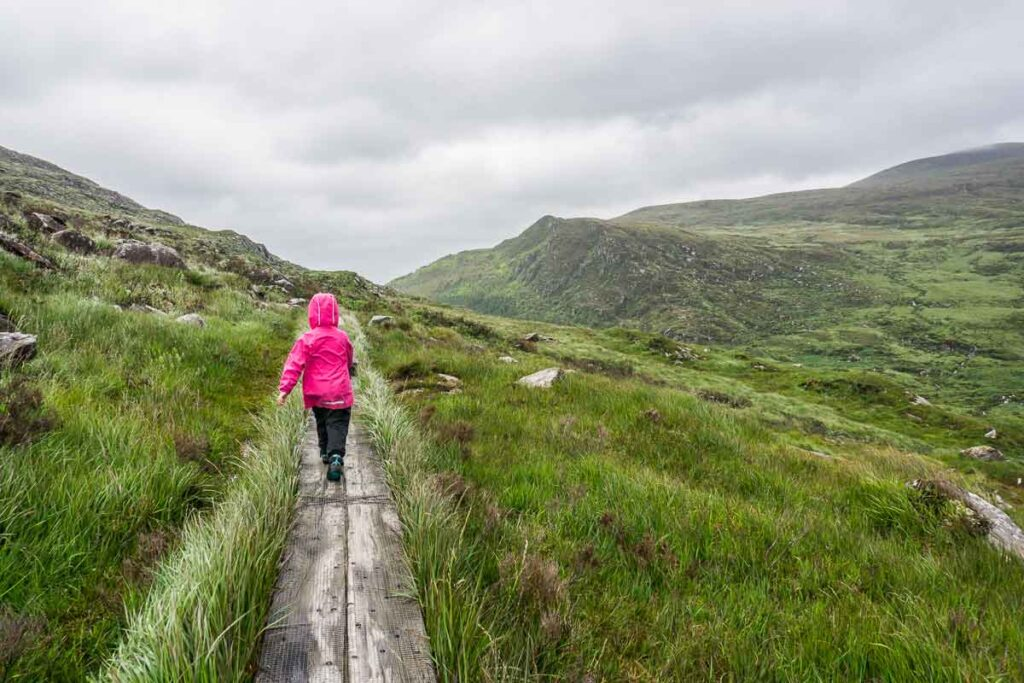 image of girl hiking boardwalks on Torc Mountain hiking trail in Killarney National Park Ireland