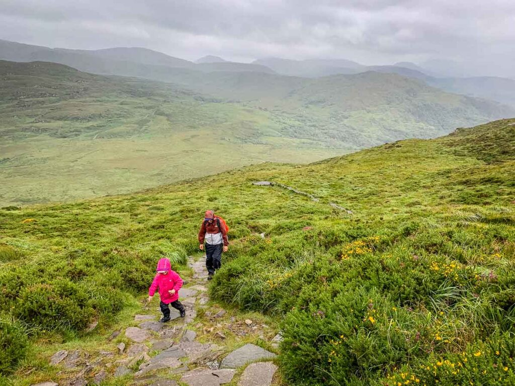 image of man and daughter hiking up Torc Mountain in Killarney National Park