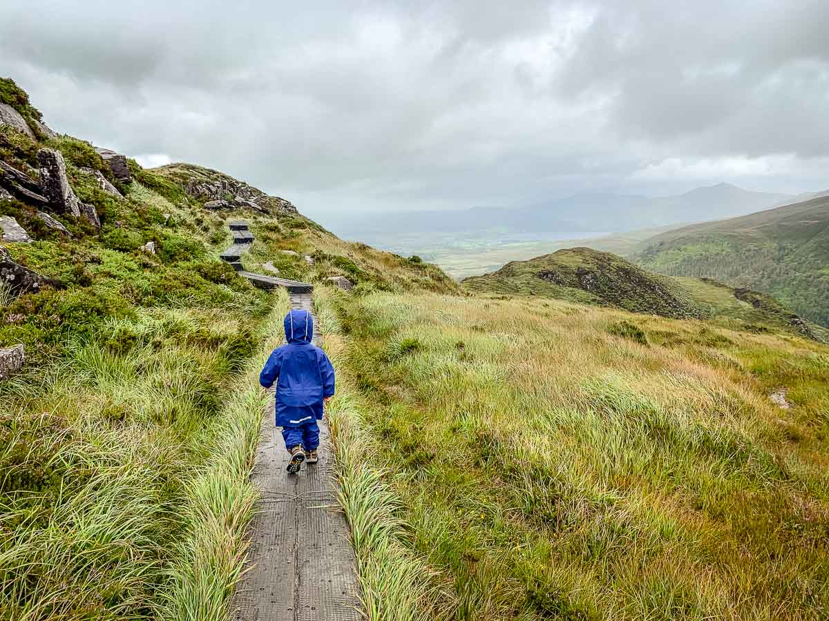 image of boy in blue rain jackethiking boardwalks on Torc Mountain hiking trail in Killarney National Park Ireland