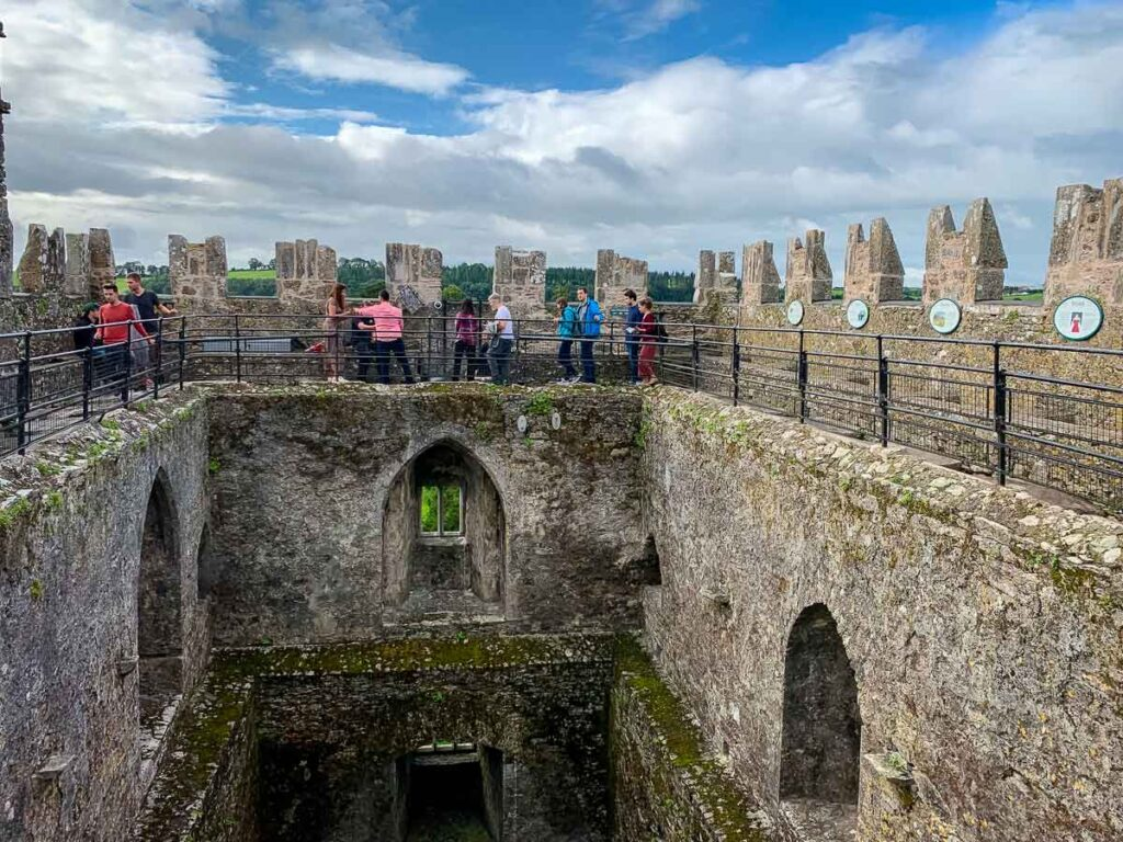 Image of people lined up to kiss the Blarney Stone at the Blarney Castle in Cork Ireland