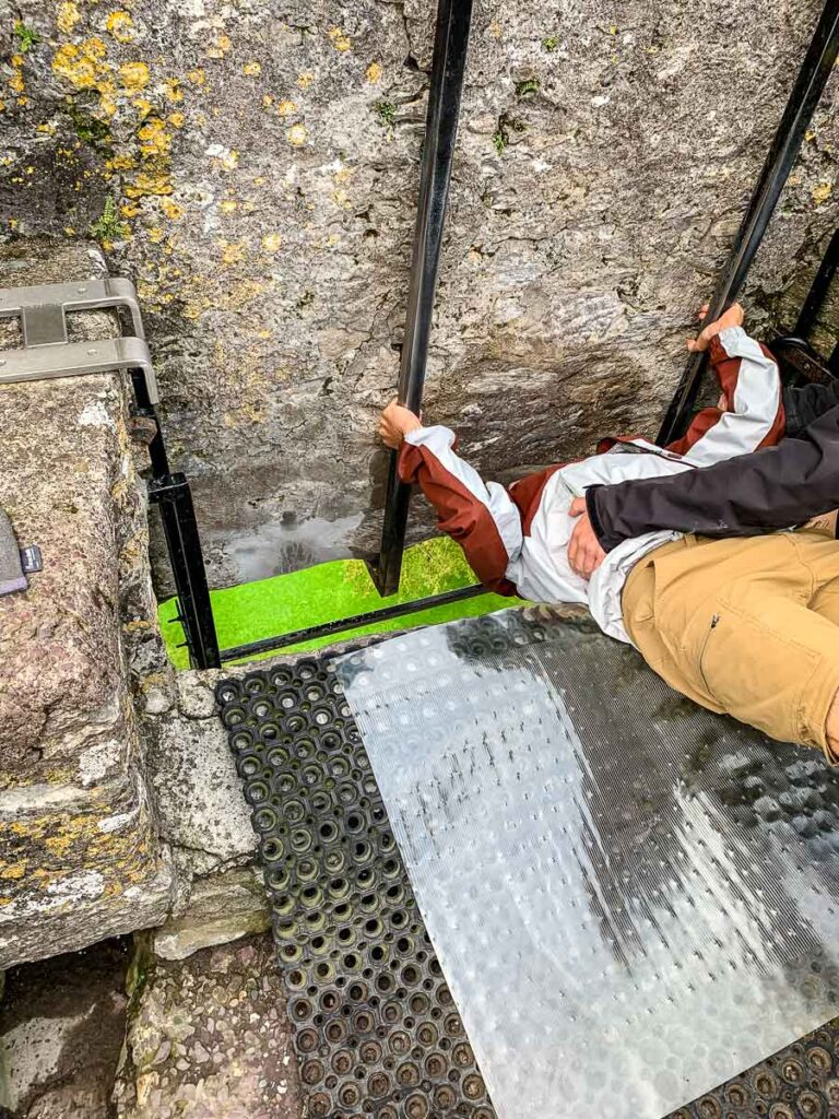 image of man lying down to kiss the Blarney Stone