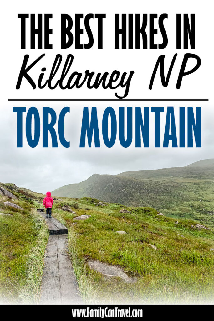 image of girl in pink rain jacket walking along wooden boardwalk on Torc Mountain hike in Killarney National Park Ireland
