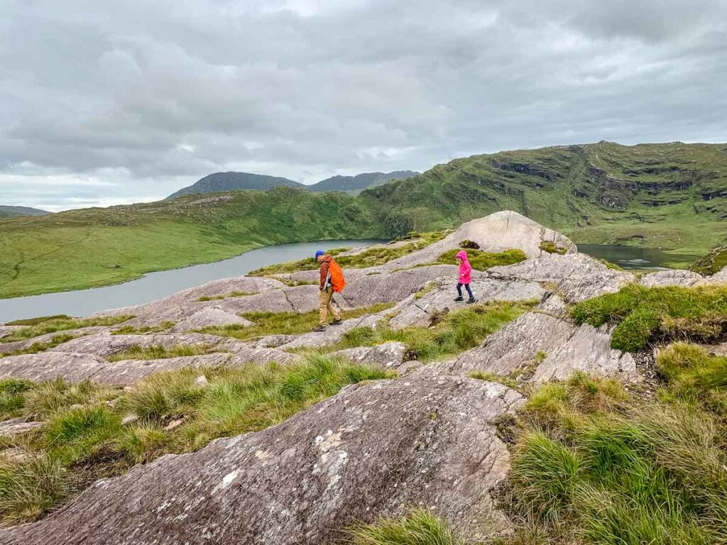 image of father and daughter walking over rocks towards Barley Lake in Ireland