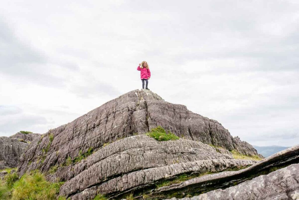 image of girl standing on top of a large rock