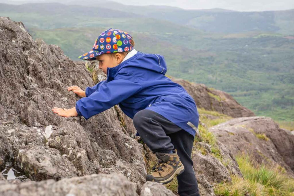 image of boy climbing rocks