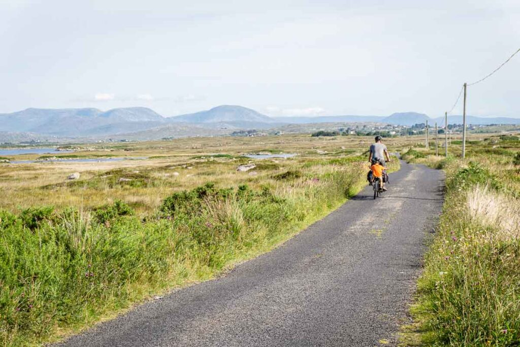 image of father cycling with boy on back of bike in Ireland