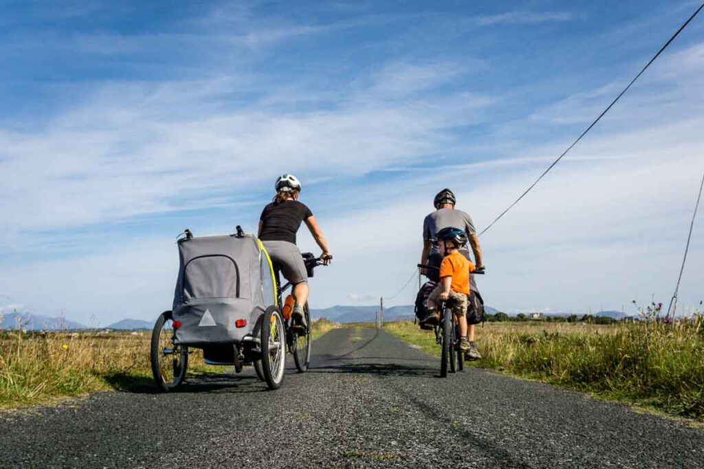 image of two parents on bikes pulling a trailer and one with a kid on a tag-a-long