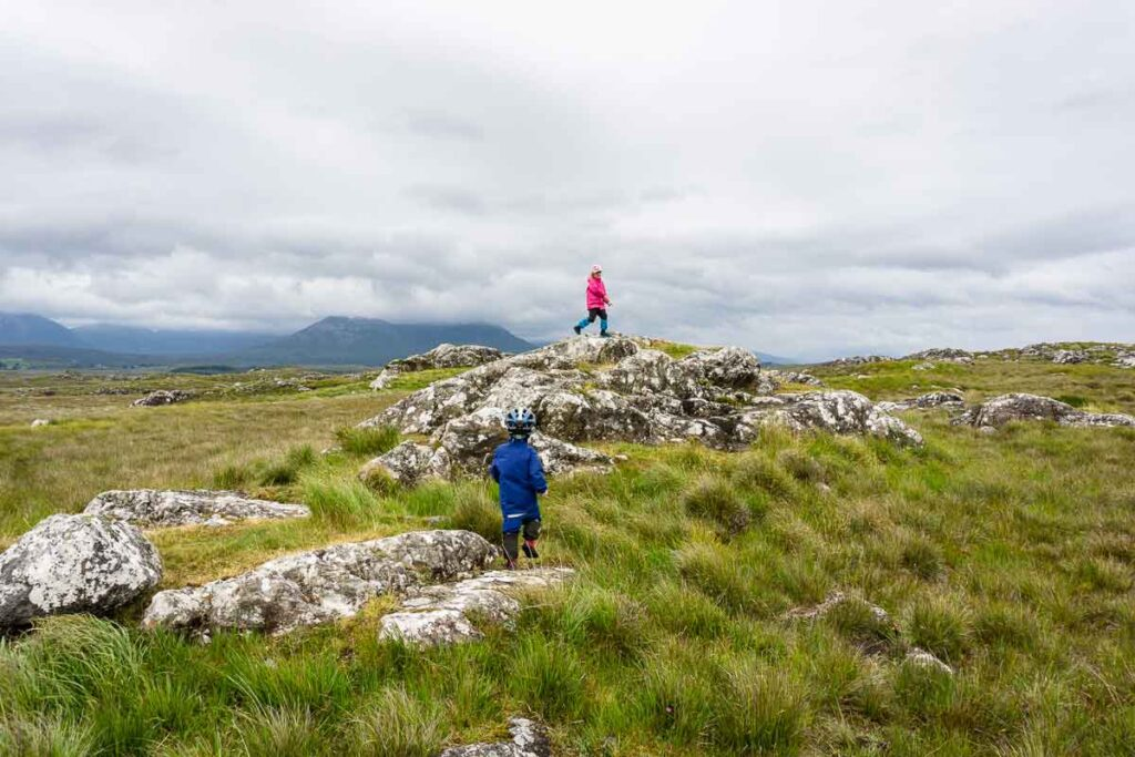 image of two kids playing on rocks in grassy field in ireland