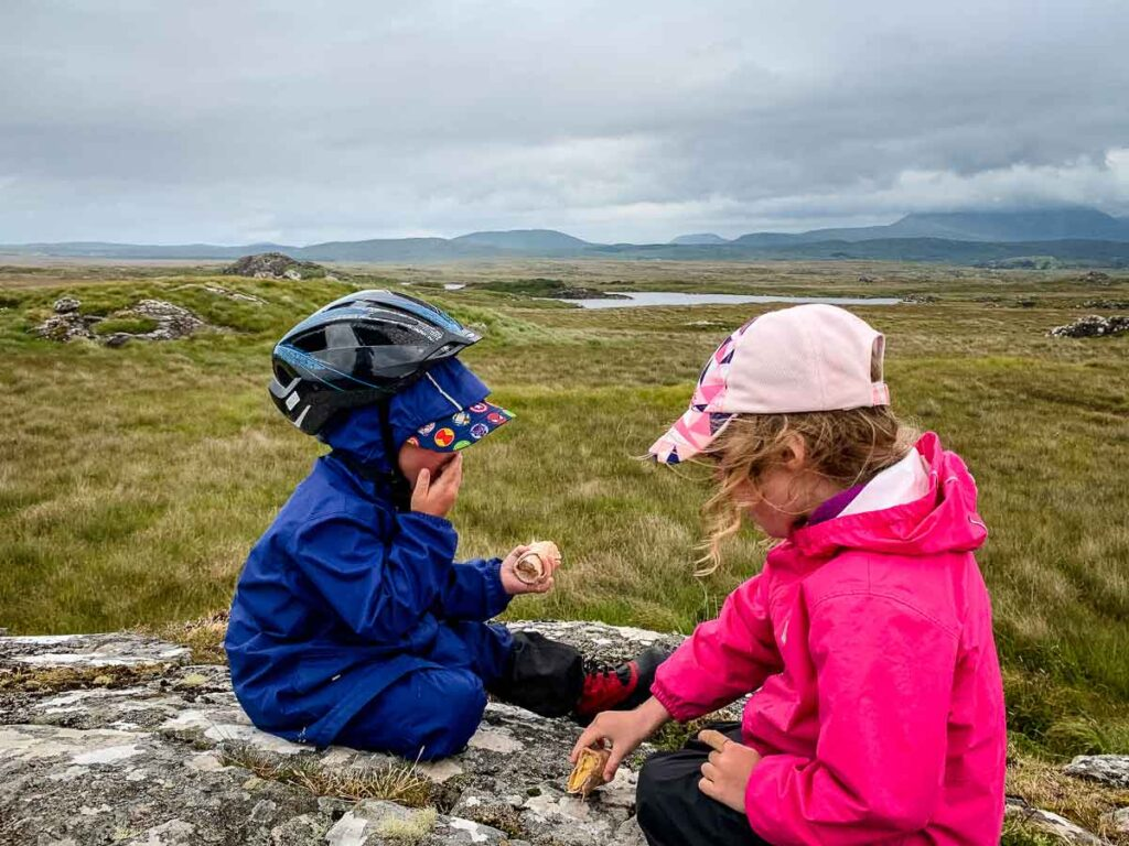 image of two kids eating lunch on a rock with views of Irish landscape in the distance