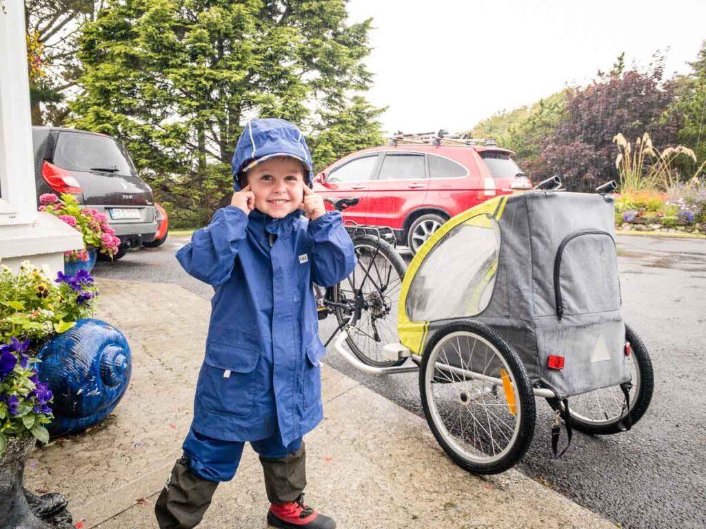 image of boy posing in front of bike trailer in rain gear