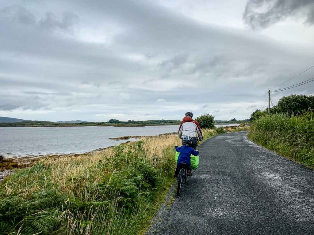 image of man cycling with boy on back of bike on tag-a-long. Cycling on the road with ocean views