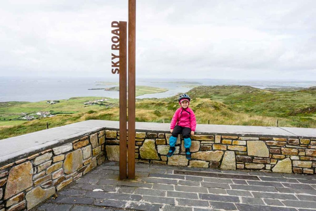 image of girl sitting on rock walk with ocean in background and next to sign that says Sky Road