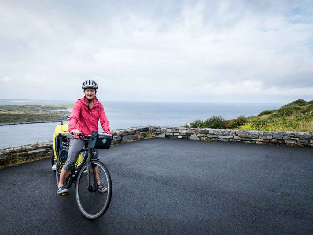 image of woman on bike pulling bike trailer in front of ocean