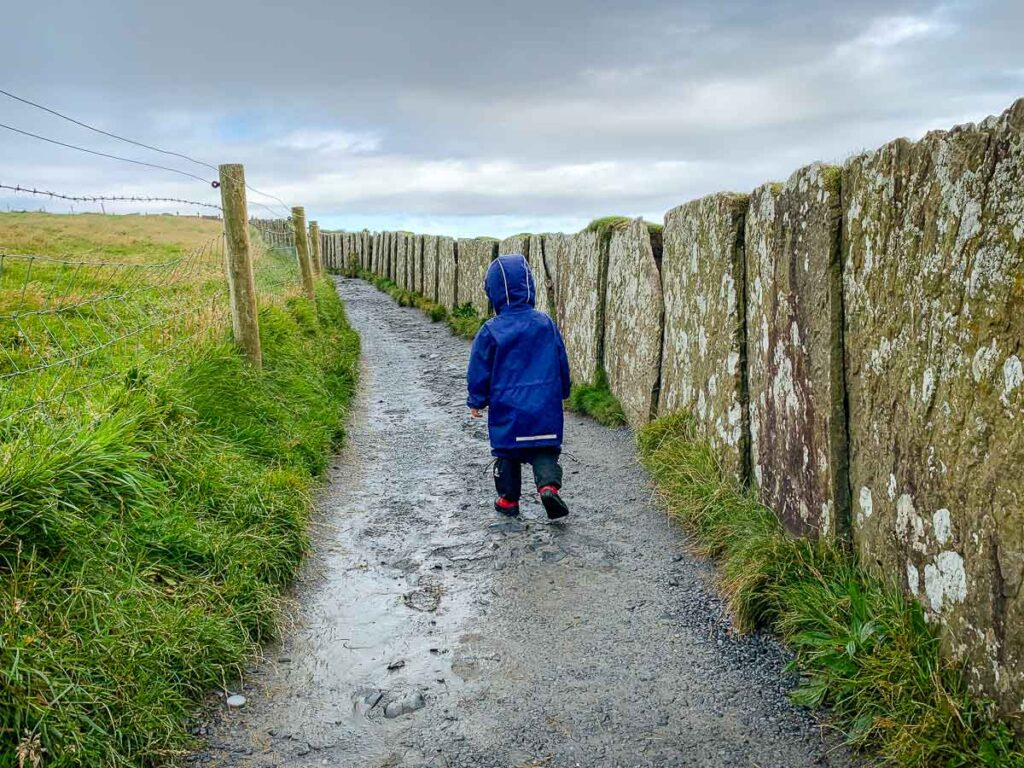 boy walking along path with grass on one side and rock wall on other side