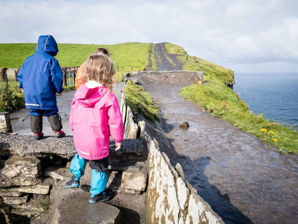image of children walking along the rock wall with path in front of them at cliffs of moher ireland