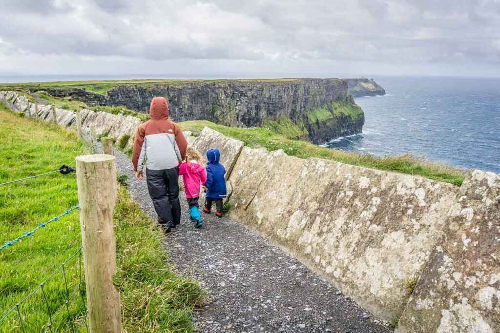 image of family walking along path with views of cliffs of moher in distance