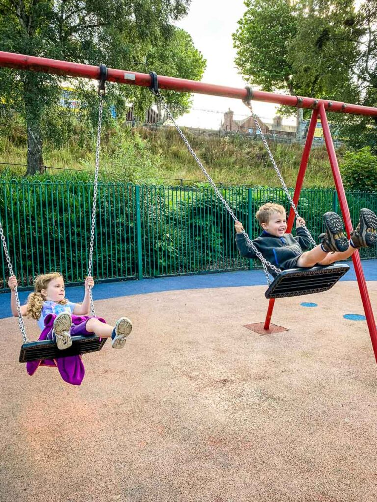 image of two kids swinging
