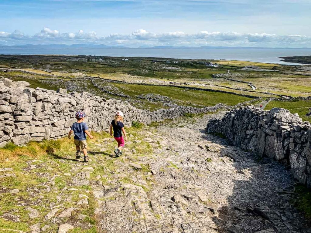 image of two children walking down rocky path with rock walls on both sides and the landscape of Aran Island in the distance