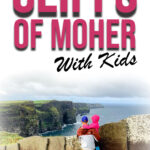 Image of Cliffs of Moher in Ireland with father holding child. Has text overlay of Cliffs of Moher with kids