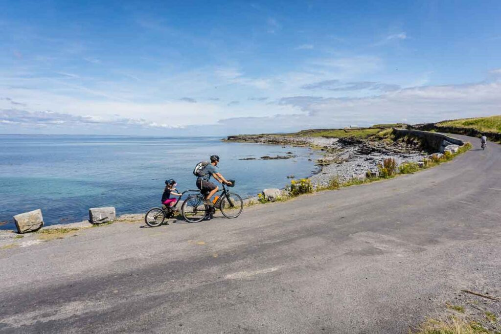 image of man cycling with child on back of bike on Aran Island Inis Mor with view of ocean