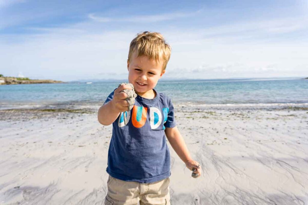 image of boy playing with sand on beach on Inishmore Aran Island Ireland