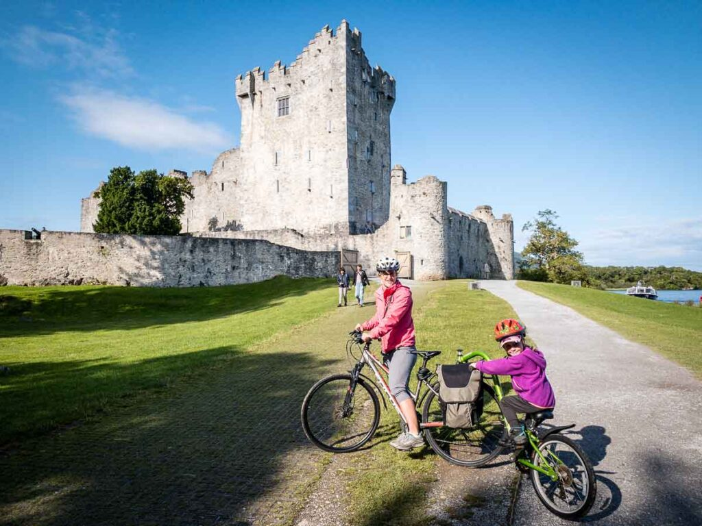 image of mother and child on bikes in front of Ross Castle in Killarney National Park
