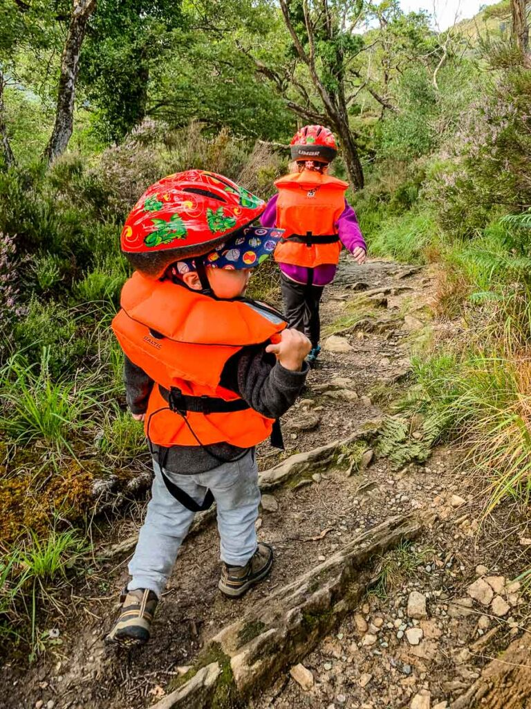 image of two children walking with life jackets on across hiking trail
