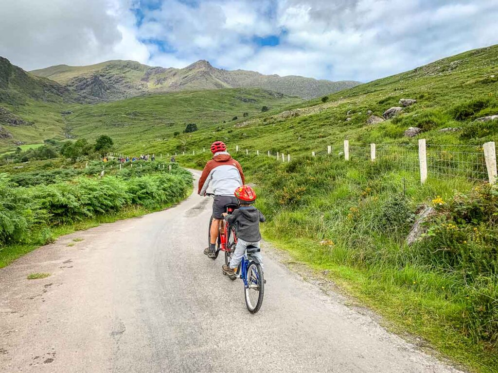 image of father cycling with child on back of bike on tag-a-long bike