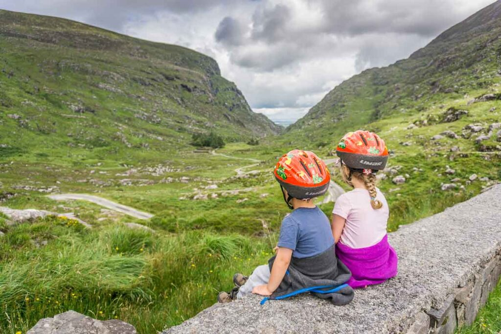image of two children with helmets sitting on rock wall overlooking landscape below