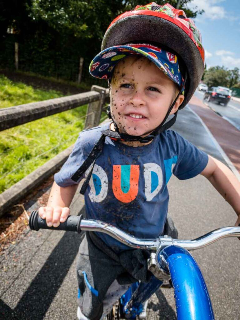 image of child covered in mud on tag-a-long bike
