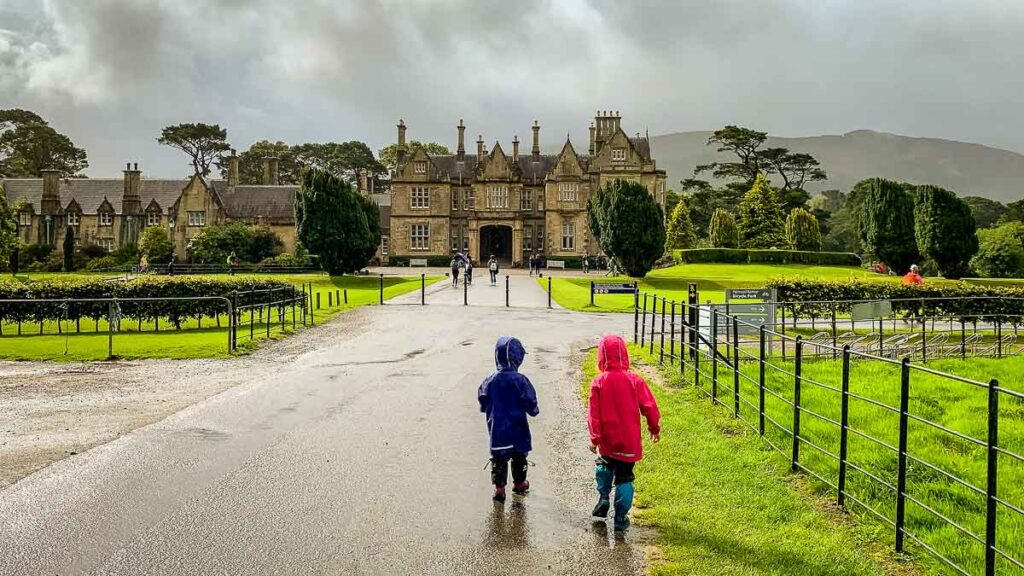 image of two kids standing in front of Muckross House in Killarney National Park Ireland