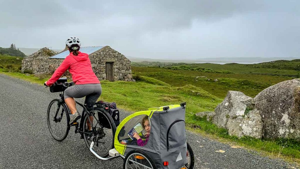 image of woman on bike pulling child trailer with Ireland landscape in the distance