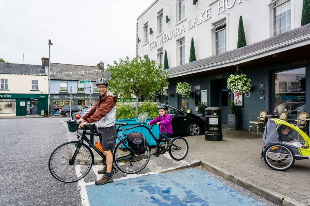 image of man cycling with girl on tag-a-long leaving hotel for family cycling holiday in ireland