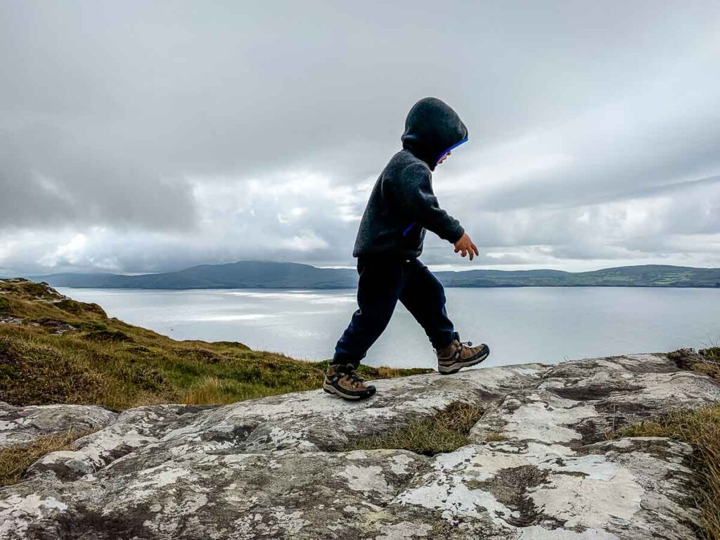 image of boy hiking on rocks on Lighthouse Loop Trail in Ireland
