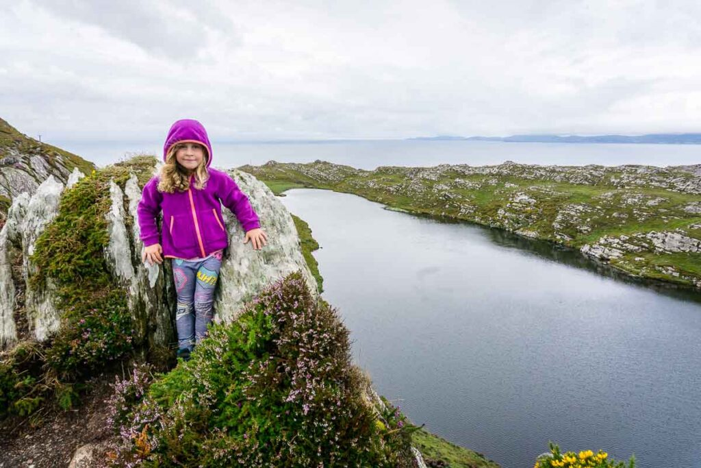 Enjoying stunning scenery while hiking in Ireland was one of our top things to do in Ireland with the family  Image of girl in front of lake with ocean in the distance on Lighthouse Loop Hike in Ireland