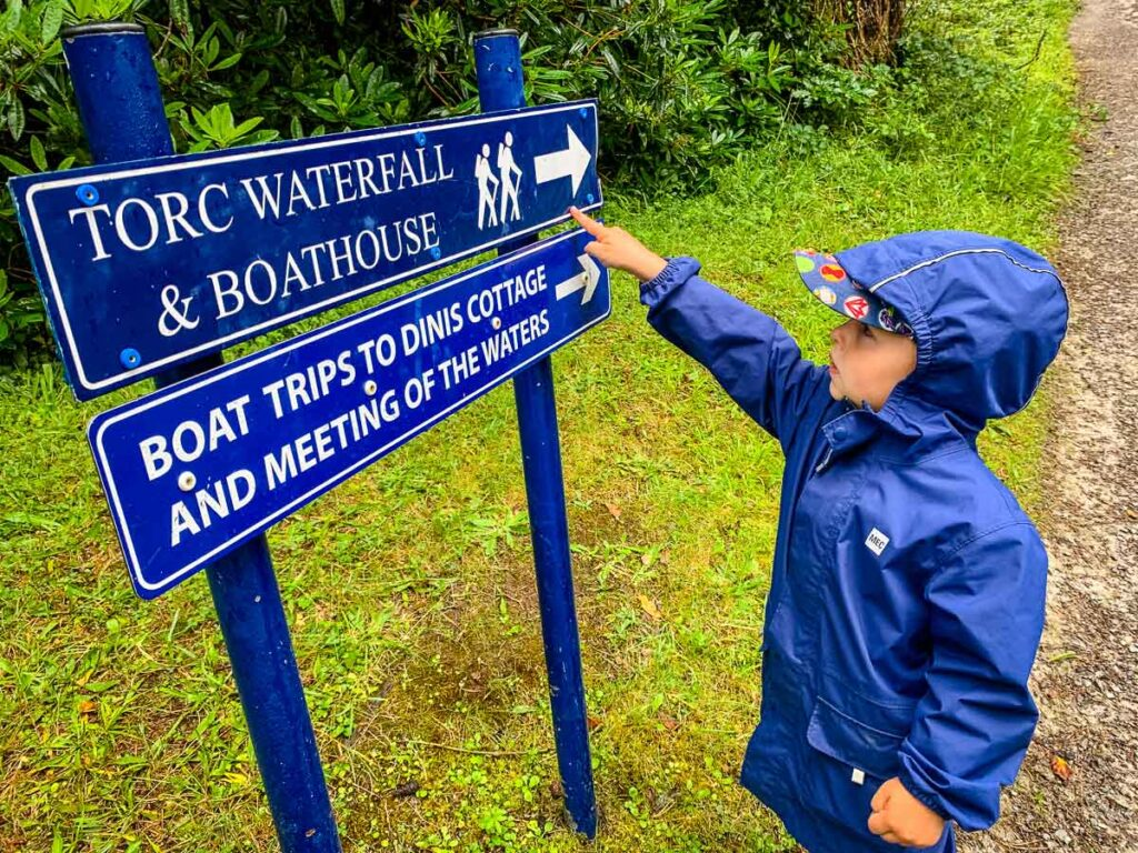 image of boy in rain gear pointing at sign for Torc Waterfall in Killarney NP Ireland
