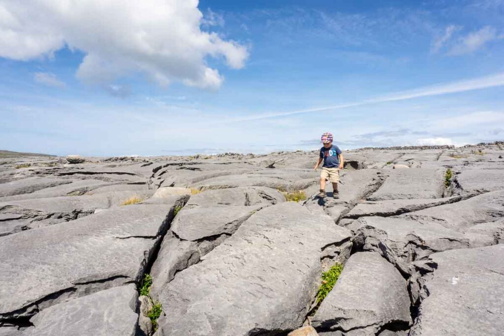 image of boy walking on rock formations on Aran Island Inishmore Ireland