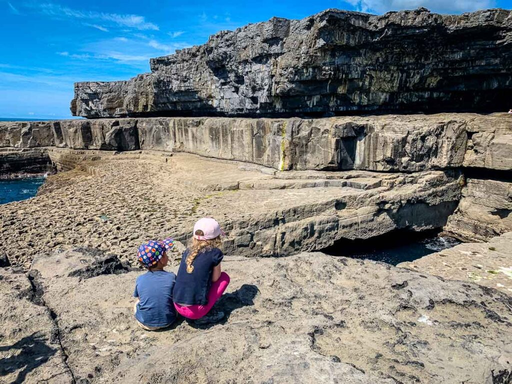 image of kids looking at wormhole on Inis Mor Aran Island Ireland
