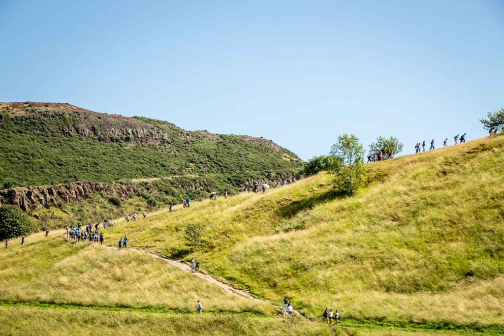 image of trail and people hiking up Arthur's Seat in Edinburgh Scotland