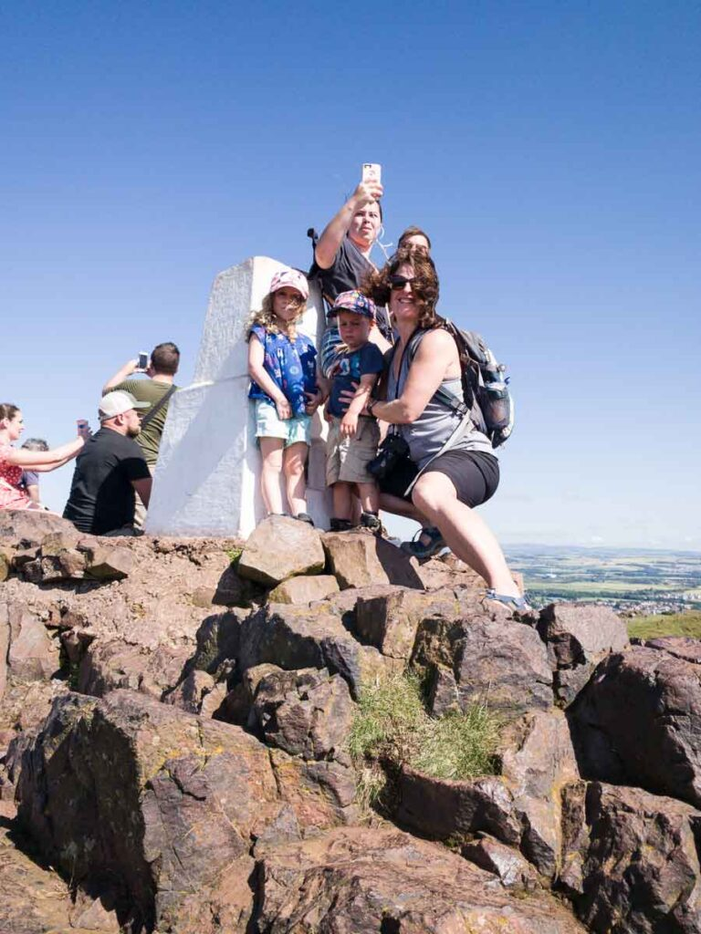 image of mother and two kids standing at the summit of Arthur's Seat in Edinburgh