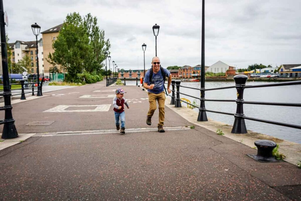 Image of father and boy running along Lagan Towpath in Belfast Northern Ireland