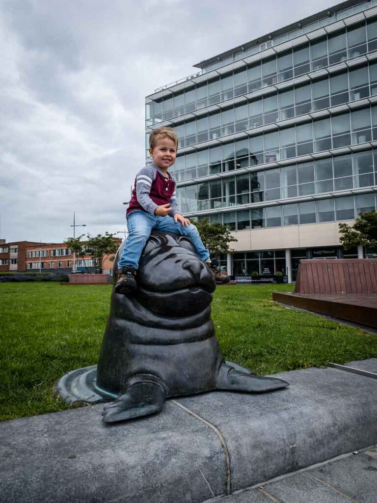 image of boy sitting on seal sculpture in Belfast with kids