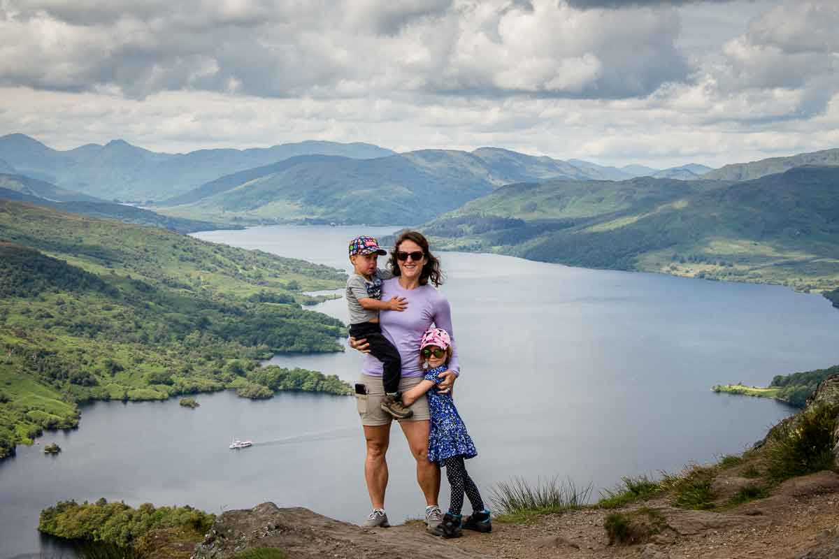 image of mom holding two kids with view of lake in the background on Ben A'an hike in the Trossachs National Park Scotland